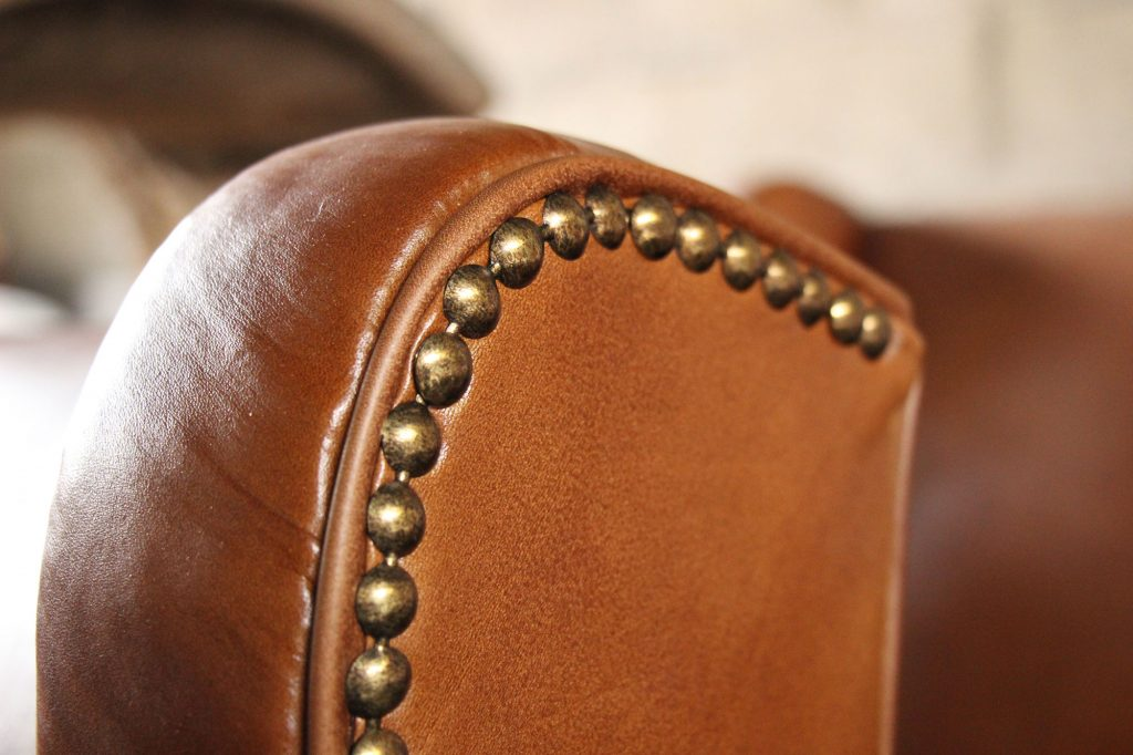 Detail of the armrest of a entirely renovated leather armchair. The leather is new and given the patina of the ancient leather color in our leather workshop in Brittany, l'Atelier du cuir - Bretagne. It is decorated with a band of brass nails.