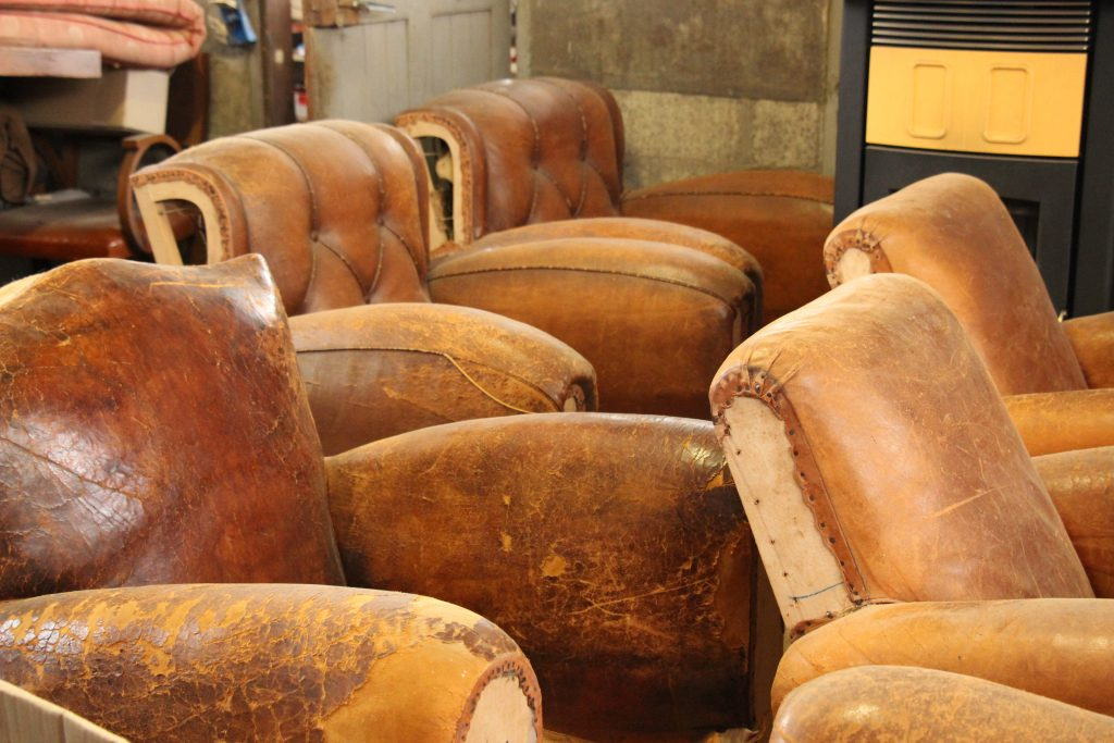 Some vintage club armchairs in old leather that await their renovation and restauration in our leather workshop in Callac, Brittany, l'Atelier du cuir - Bretagne.