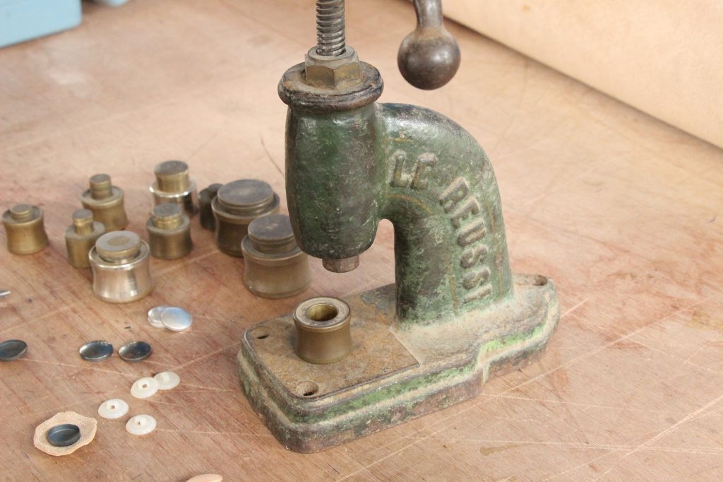 Old button machine to fabricate leather covered buttons. We make all the leather buttons ourselves for all our vintage furniture in leather in our leather workshop in Brittany, l'Atelier du cuir - Bretagne.